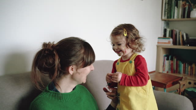 little girl puts face paint on mum's cheek - annual event stock videos & royalty-free footage