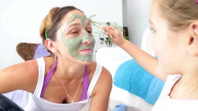 little girl puts mud face mask on mom - spa treatment stock videos & royalty-free footage