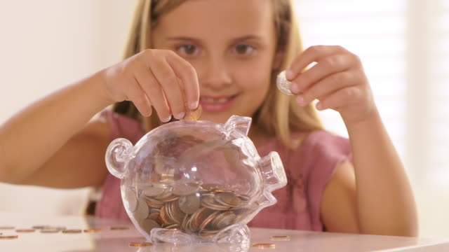 little girl putting coins into piggy bank. - piggy bank stock videos & royalty-free footage