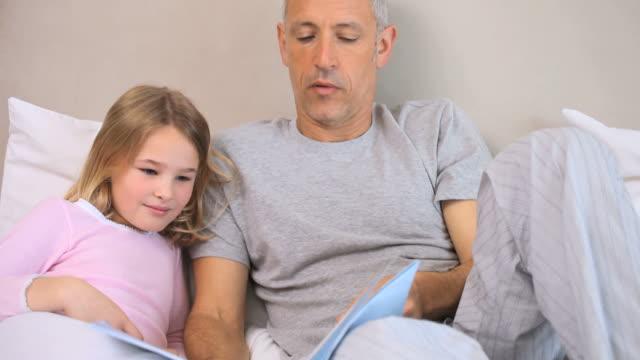vídeos de stock e filmes b-roll de little girl reading a book aloud - cabelo branco