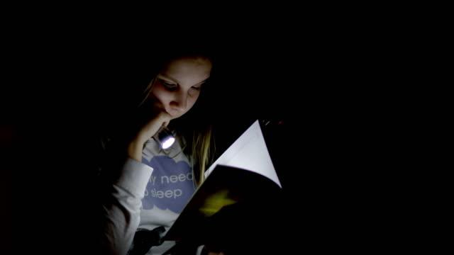 ms はほとんど女の子が懐中電灯で本を読んで - one teenage girl only点の映像素材/bロール