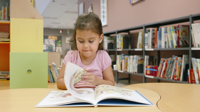 ds little girl reading at the children's table in a public library - picture book stock videos and b-roll footage