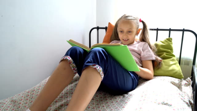 Kleine Mädchen-Lesebuch in ihrem Zimmer.