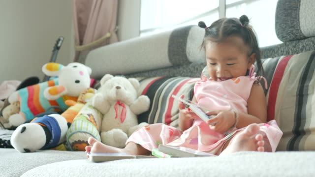 little girl reading book in living room - alertness stock videos and b-roll footage