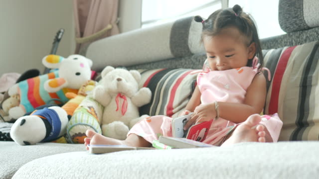 vídeos de stock e filmes b-roll de little girl reading book in living room - 18 a 23 meses