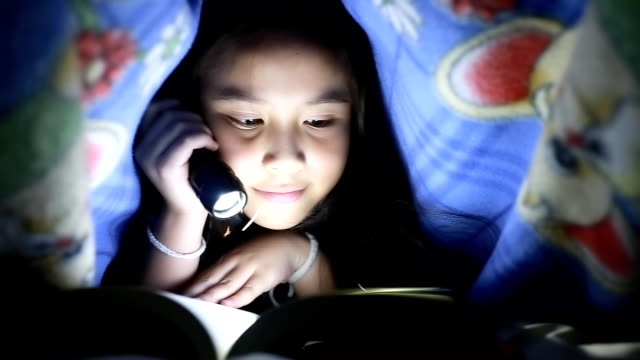 Little girl reading book under the blanket
