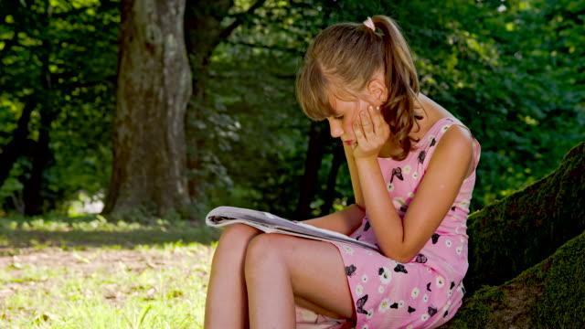MS DS kleines Mädchen lesen im Park