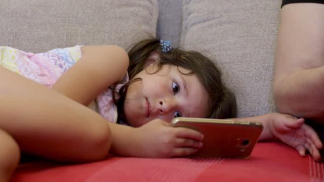 小さな女の子が休んで、スマートフォンを見て - 横向きに寝る点の映像素材/bロール