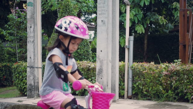ms ts little girl riding bicycles - cycling helmet stock videos & royalty-free footage