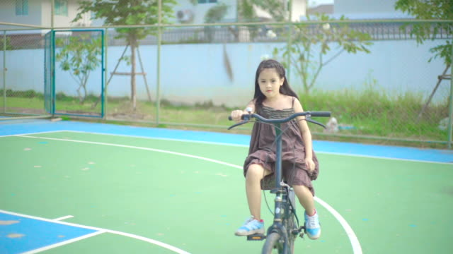A little girl riding her bicycle in playgrounds.