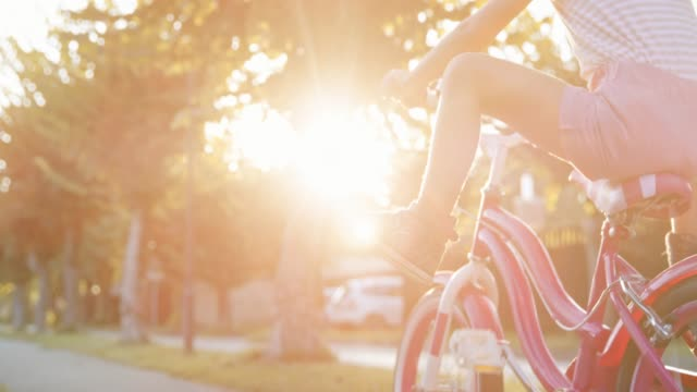 slo mo little girl riding her bike, pushing the pedals and then raising her feet in the air - low section stock videos & royalty-free footage