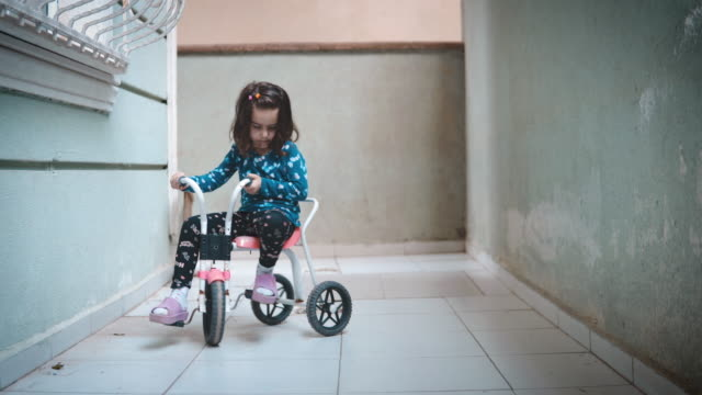 little girl riding tricycle on balcony. feeling lonely because she is not allowed to go outside and play. - tricycle stock videos & royalty-free footage