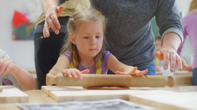 vídeos y material grabado en eventos de stock de ds niña rodando un pedazo de arcilla en el aula con la ayuda de su maestro - menos de diez segundos