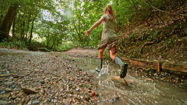 slo mo little girl running across  a creek in rain boots - dress stock videos & royalty-free footage