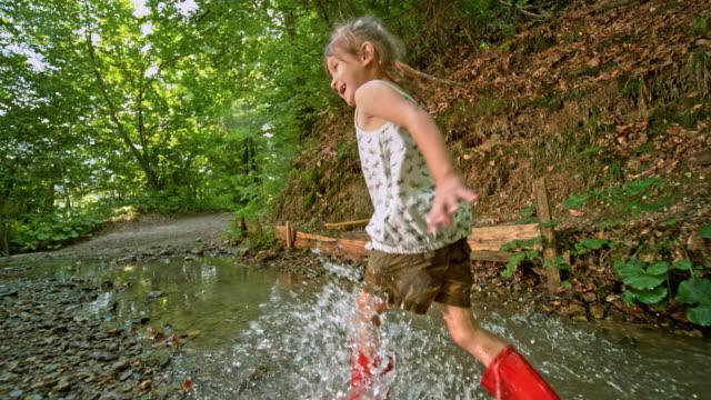 vídeos de stock, filmes e b-roll de slo mo pov menina atravessando um riacho vermelho chuva botas - galho