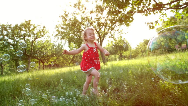 slo mo little girl running after soap bubbles in the orchard in setting sun - toddler stock videos & royalty-free footage