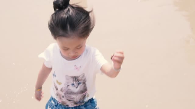 little girl running and collect shells on the beach - seashell stock videos & royalty-free footage