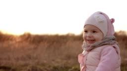 Little girl running and laughing at sunset in slow motion in pink clothing