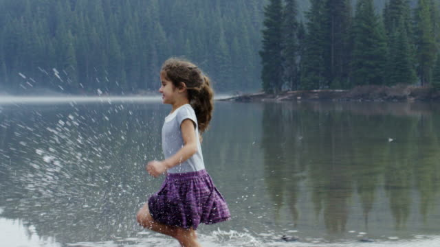 Little girl running and playing in the shallow water.