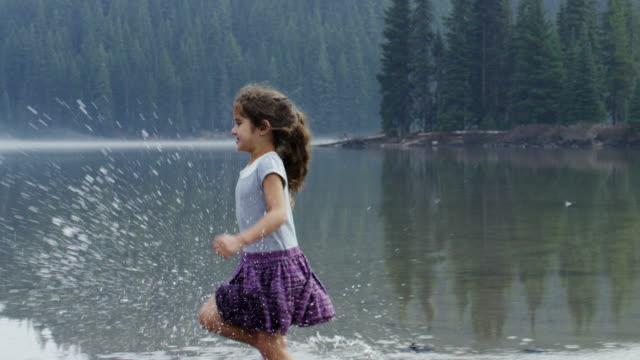 kleines mädchen laufen und spielen im flachen wasser. - waten stock-videos und b-roll-filmmaterial