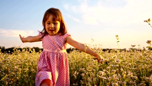 SLO MO Little girl running in fields with arms outstretched