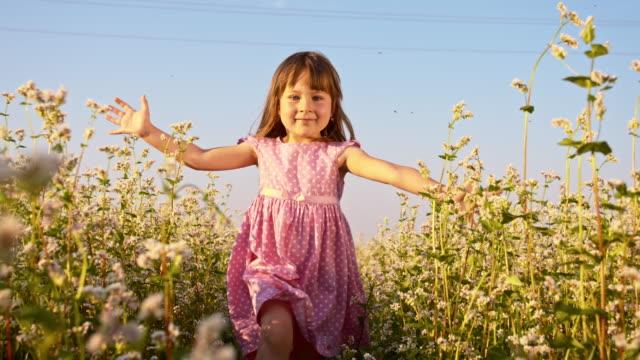 SLO MO Little girl running in the buckwheat field