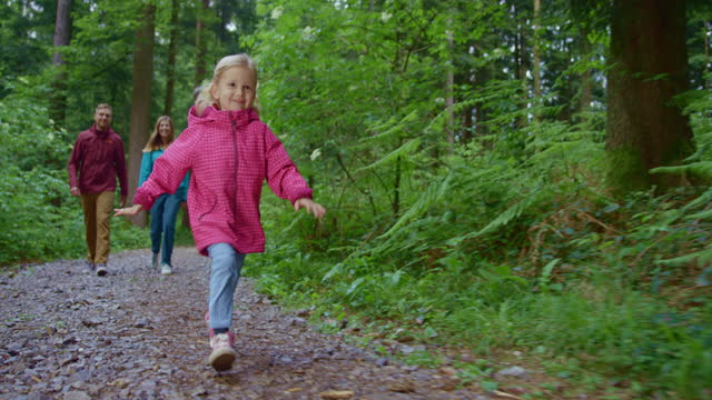 slo mo ts little girl running in the forest and her parents walking in the background - hood clothing stock videos & royalty-free footage