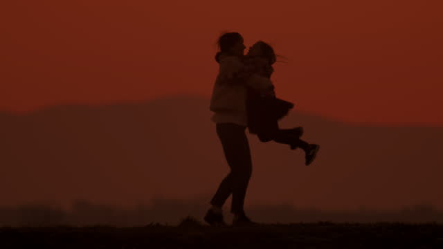 vídeos de stock, filmes e b-roll de slo mo ls menina correndo para os braços da mãe em uma colina ao anoitecer - virar