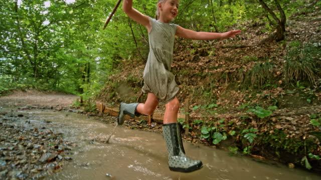 vídeos de stock, filmes e b-roll de slo mo garota correndo em um caminho de floresta e em um riacho - galho