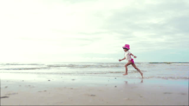 vídeos de stock e filmes b-roll de little girl running on beach - areia