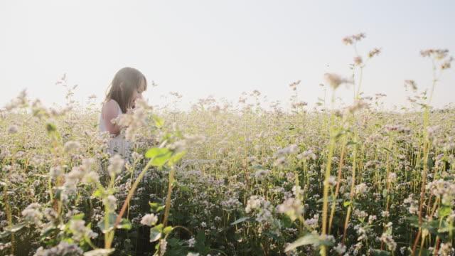 Little girl running through buckwheat field