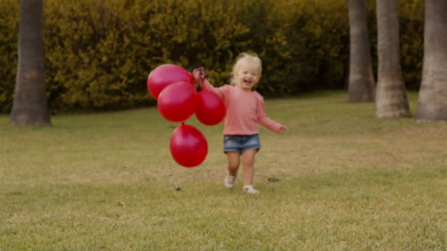 little girl running to camera with red balloons in park - palloncino video stock e b–roll