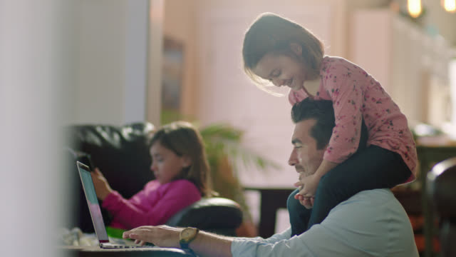 MS. Little girl runs and climbs on her dad's shoulders as he works on his laptop in family living room.
