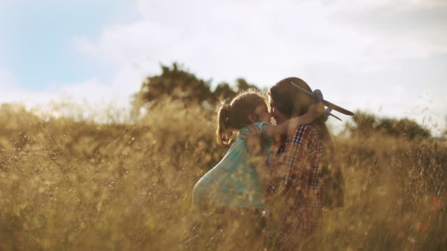 vídeos de stock e filmes b-roll de a little girl runs into her mother's arms, holding a toy airplane in her hands - mãe