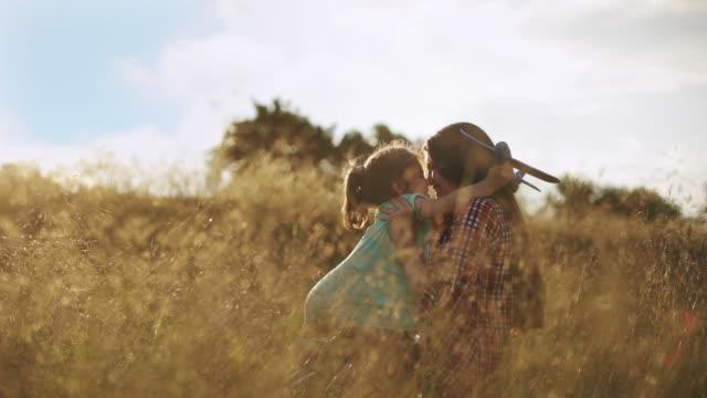 vídeos y material grabado en eventos de stock de una niña se encuentra con los brazos de su madre, sosteniendo un avión de juguete en sus manos - daughter