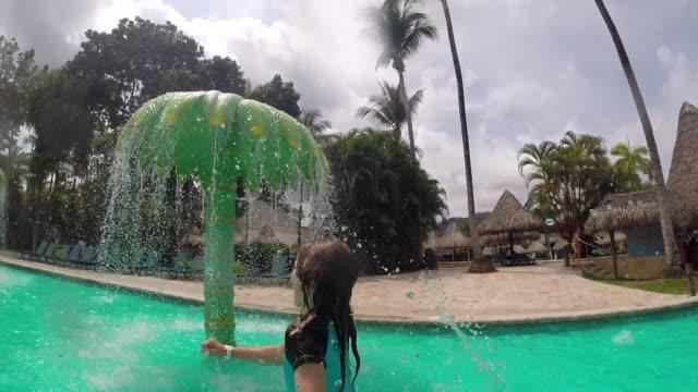vidéos et rushes de little girl runs through a waterpark then falls into the water. - kelly mason videos