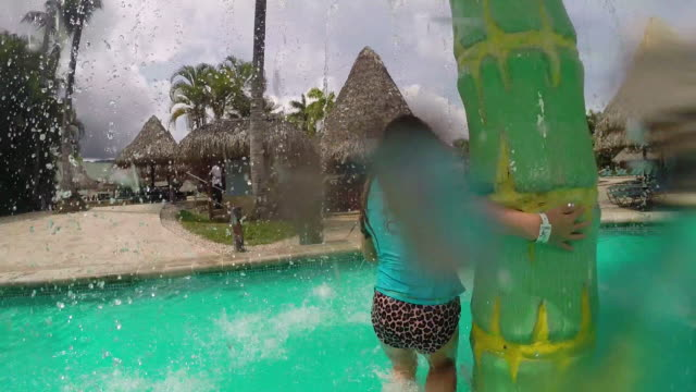 little girl runs through palm tree waterpark and father picks her up and throws her in the air then lets her down into the water. - kelly mason videos stock videos & royalty-free footage