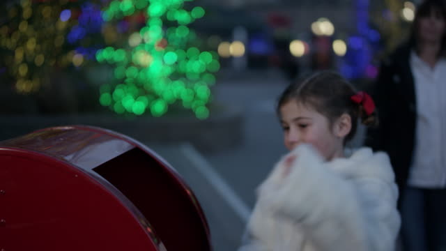 Little girl runs up to mail letter to Santa Claus