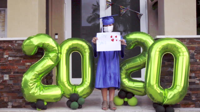 little girl school graduation in front of her house during lockdown 2020 - cap stock videos & royalty-free footage