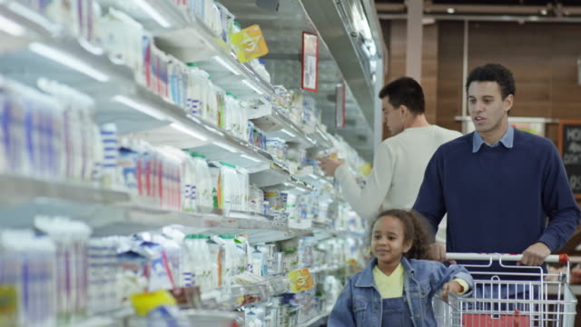 little girl shopping in supermarket with dad - milk bottle stock videos & royalty-free footage