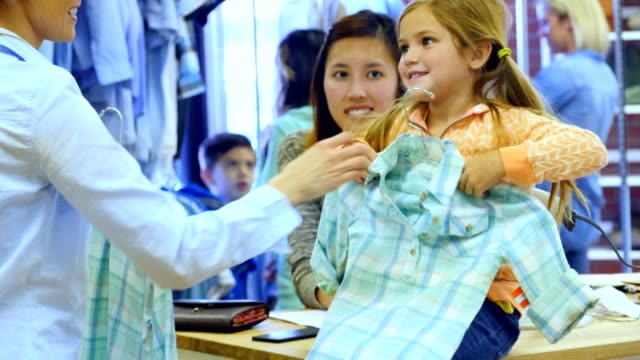 Little girl shops in department store with her mom