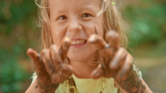 slo mo little girl showing her muddy hands and laughing - mischief stock videos & royalty-free footage
