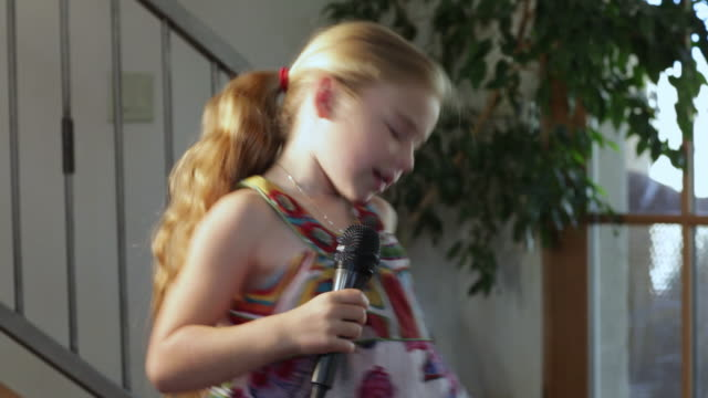 MS TS TU TD Little girl singing and dancing with microphone / Lamy, New Mexico, United States