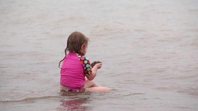 vídeos y material grabado en eventos de stock de ms little girl siting in wavebreak and playing with sand in her hand / toronto, ontario, canada - kelly mason videos