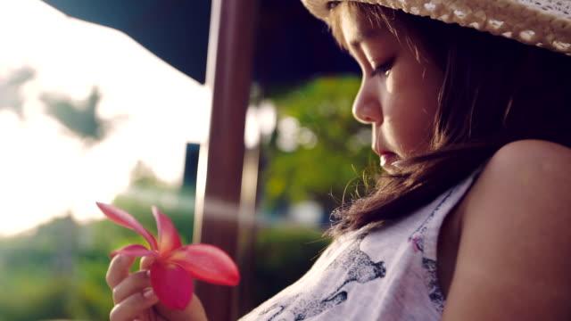 vidéos et rushes de une petite fille assise et tenant une fleurs - un jour comme les autres images en série