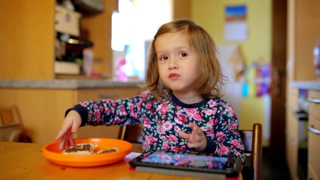 little girl sitting at kitchen table with ipad eating cereal - spread food stock videos and b-roll footage