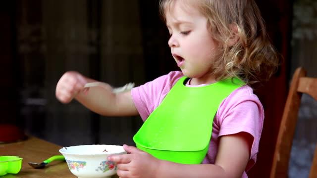 vidéos et rushes de petite fille s'asseyant derrière la table et mangeant la nourriture - 2 3 ans