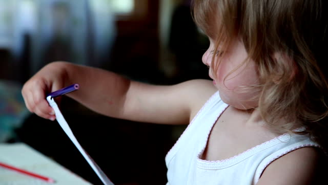 little girl sitting behind the table and holding a pencil drawing in hands - pencil drawing stock videos & royalty-free footage