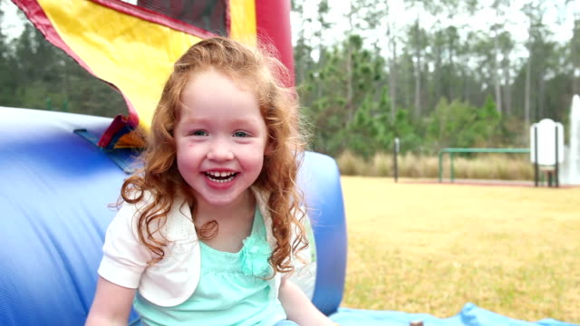 Little girl sitting by bounce house, waving at camera