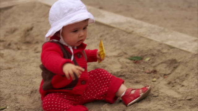 a little girl sitting in a sandpit playing stockholm sweden. - only baby girls stock videos & royalty-free footage